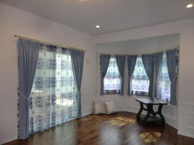 白い壁面に栄える上品な大柄ブルーのシアーカーテン